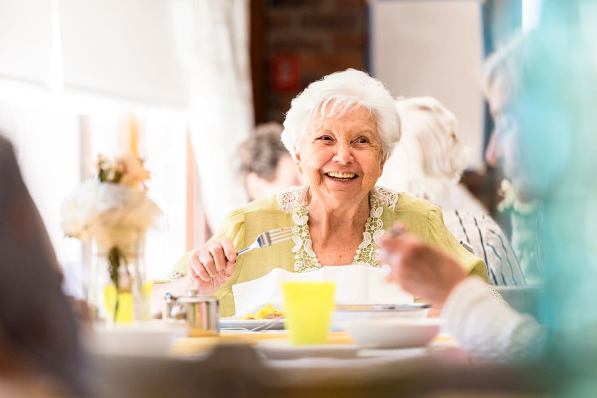 A memory care resident in the dining hall at Oxford Glen Memory Care at Sachse in Sachse, Texas