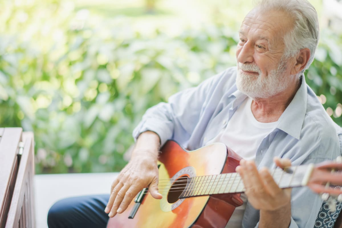 Resident playing the guitar at Oxford Glen Memory Care at Grand Prairie in Grand Prairie, Texas