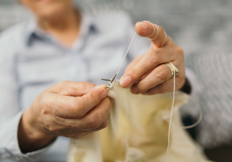 Senior sewing clothes by hand at Seven Lakes Memory Care in Loveland, Colorado