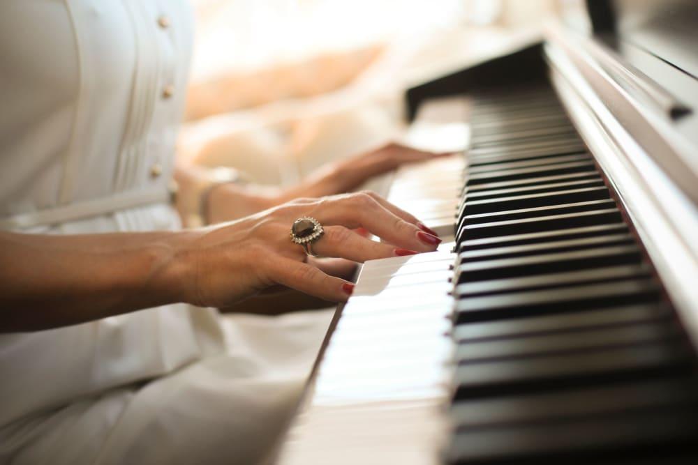 senior resident playing the piano at The Vista in Esquimalt, British Columbia.