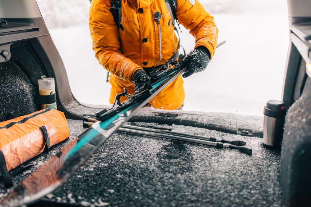 A customer putting skis in a car near Storage Star Forest Lane in Dallas, Texas