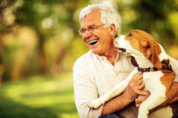 A smiling resident with his dog at The Legacy at Southpointe Drive in Greenville, South Carolina