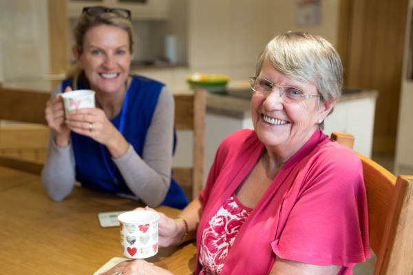 Resident drinking coffee with a caretaker at Generations at Lewiston in Lewiston, Idaho