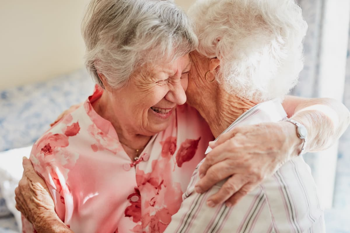 Two residents hugging at Sandpiper Courtyard in Mt. Pleasant, South Carolina