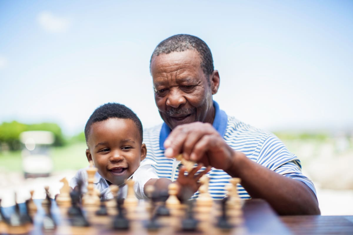 A resident teaching his grandson how to play chess at The Oxford Grand Assisted Living & Memory Care in Kansas City, Missouri