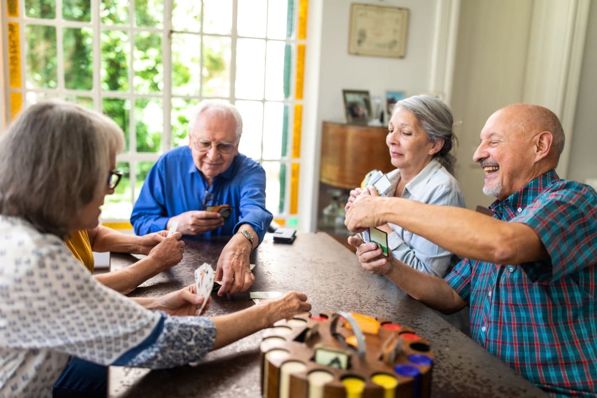 Residents laughing and playing a game at CERTUS Premier Memory Care Living in Mount Dora, Florida.