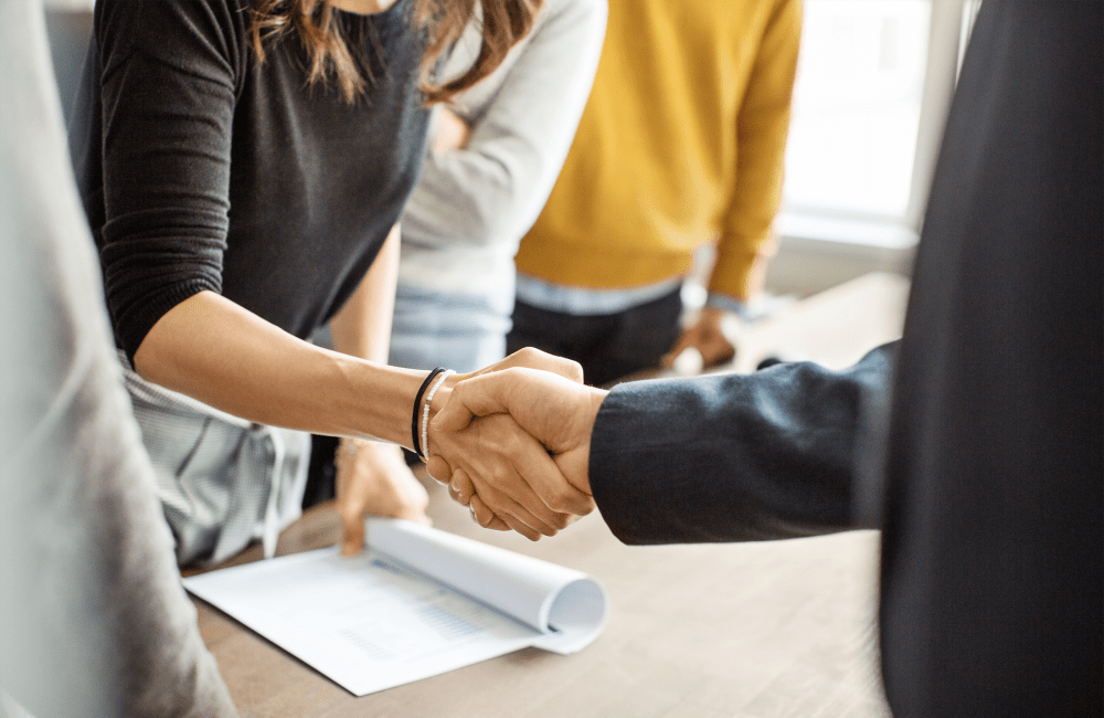 Businesspeople shake hands after a productive sales meeting.