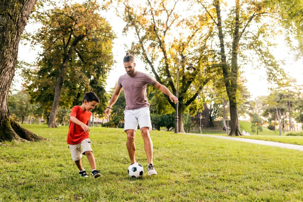 Father and son playing soccer at a park near The 450 in Lombard, Illinois