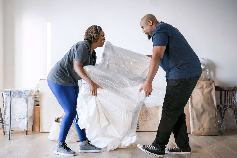 A couple moving a couch while unpacking from their storage unit at South Bank Secure Storage in Rifle, Colorado
