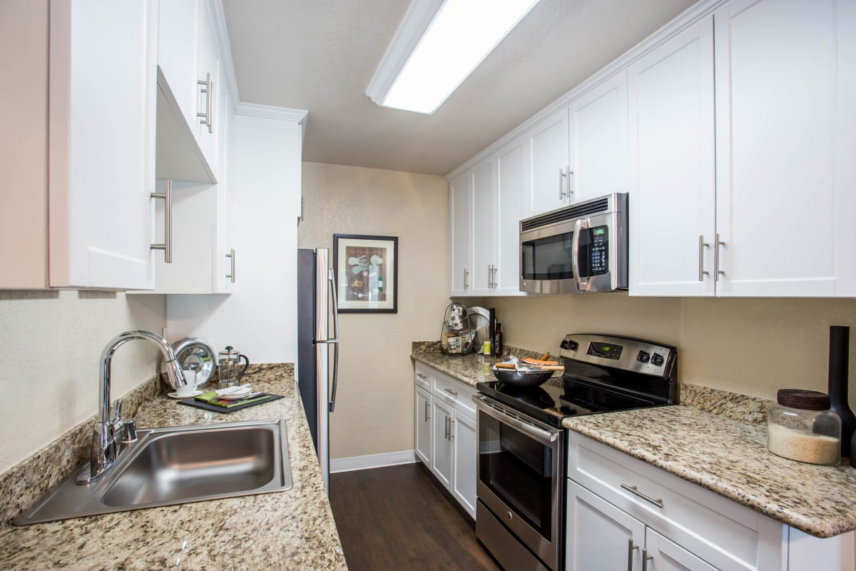 Modern kitchen with granite countertops and stainless-steel appliances in a model home at Valley Plaza Villages in Pleasanton, California