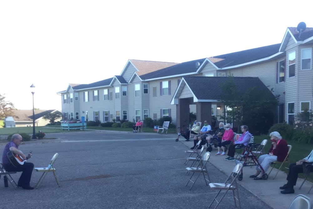 Resident sitting oustide to listen to music at Whispering Oak Place in Ellendale, Minnesota