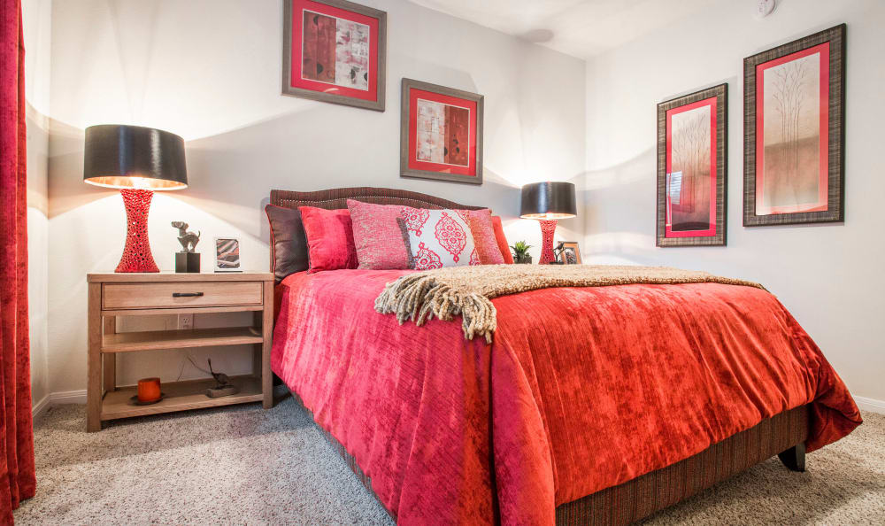 Well-decorated bedroom with plush carpeting in a model home at Riata Austin in Austin, Texas