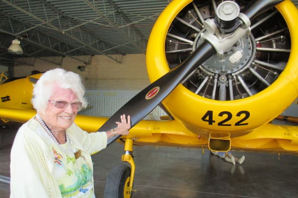 A resident from Cedarview Gracious Retirement Living in Woodstock, Ontario touching a plane propeller