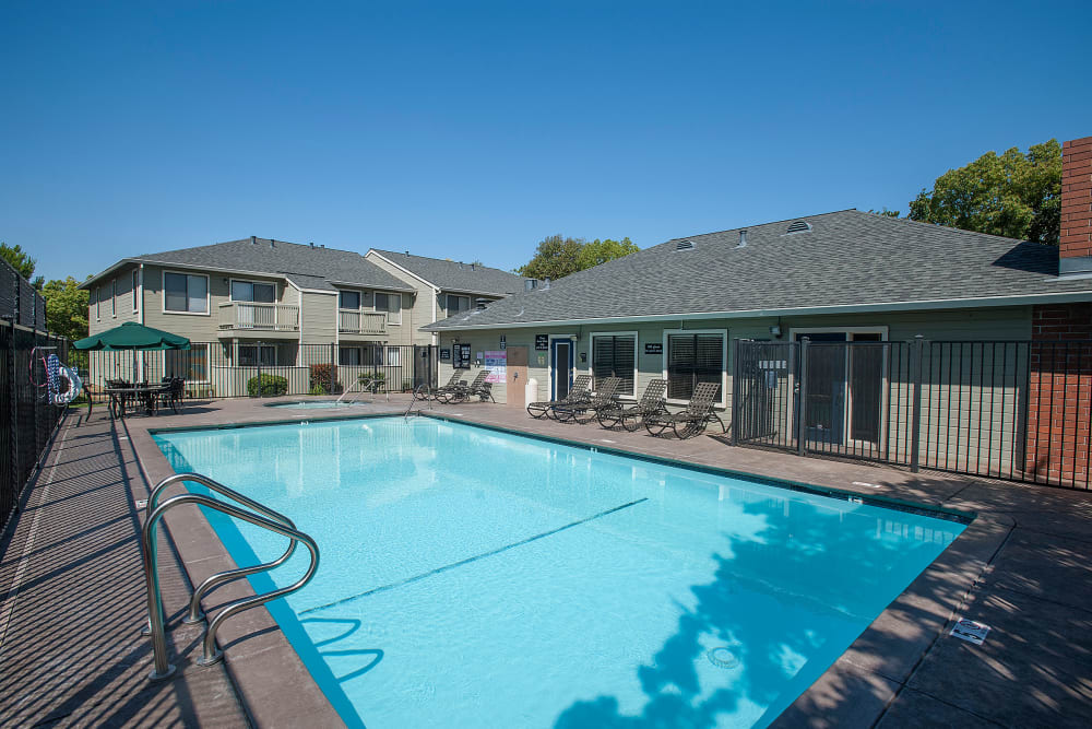 Sundeck with a umbrellas for shade at Sandpiper Village Apartment Homes in Vacaville, California