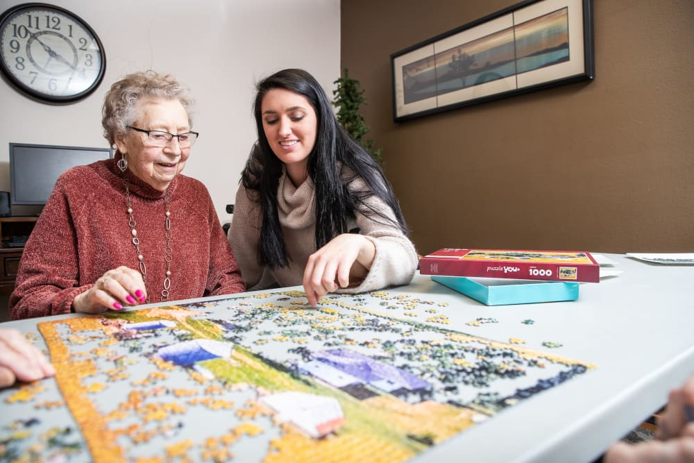 Resident and daughter putting a puzzle together at Parker Place in Parkersburg, Iowa