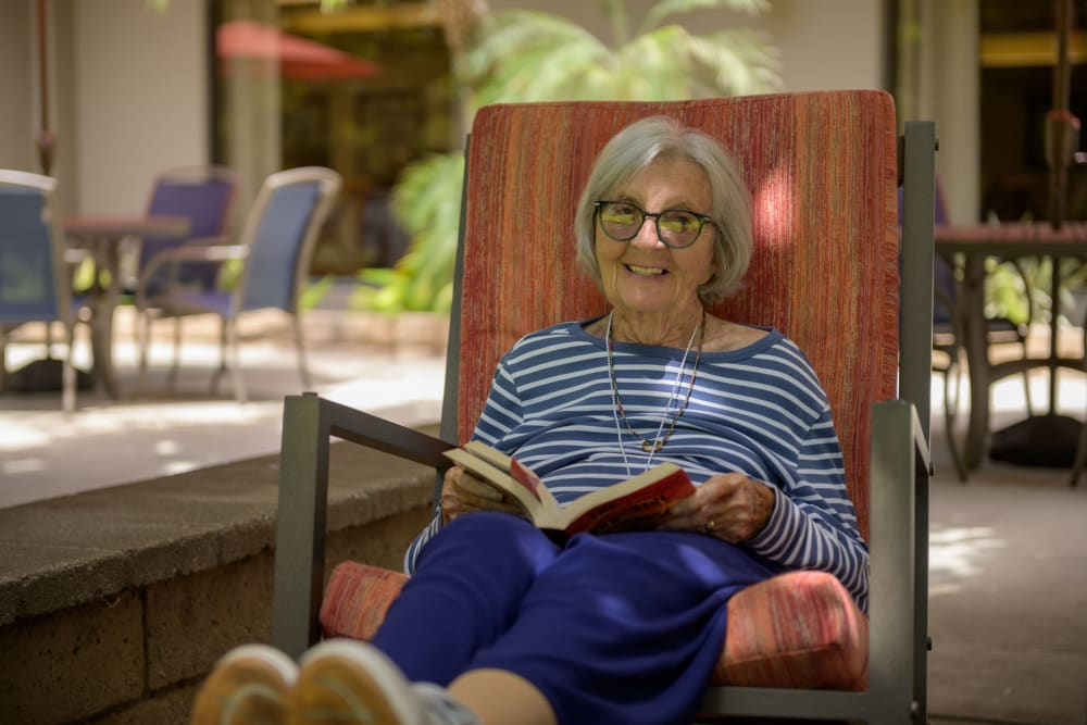Resident of WellQuest of Elk Grove enjoying a book in Elk Grove, California