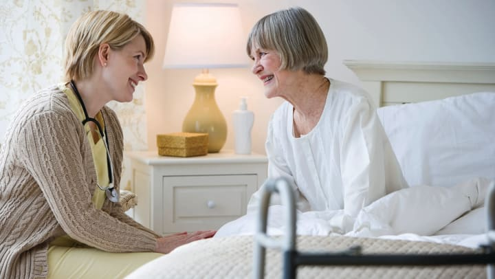 Caregiver happily helping a resident in her bed