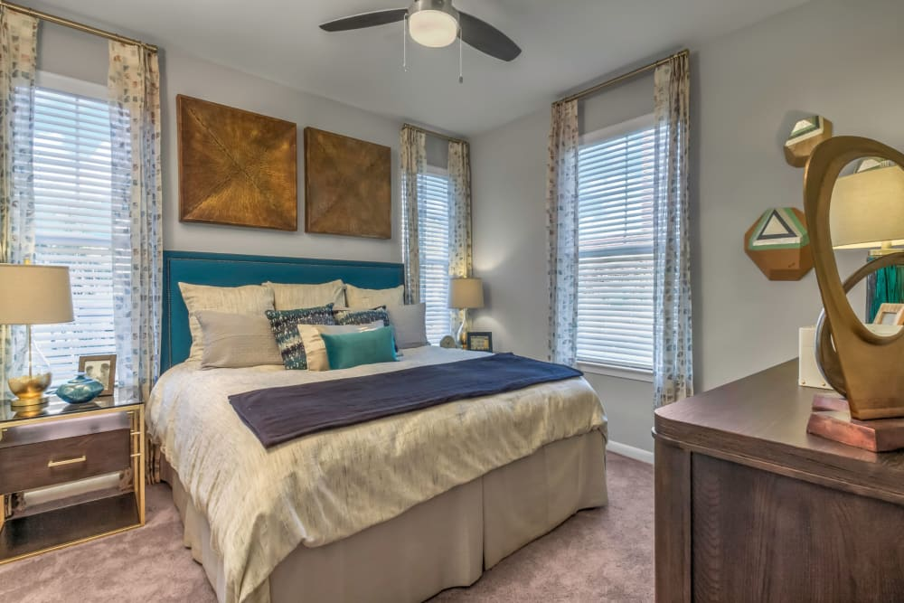Plush carpeting and a ceiling fan in a model home's bedroom at The Palmer in Charlotte, North Carolina
