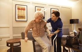 Caregiver helping a resident out of bed