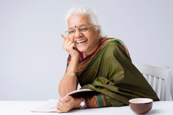 Lady sitting at table with a tea cup laughing at The Retreat at Carolina Bay in Hartsville, South Carolina