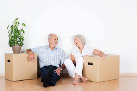 Elderly couple sitting in their home with moving boxes.
