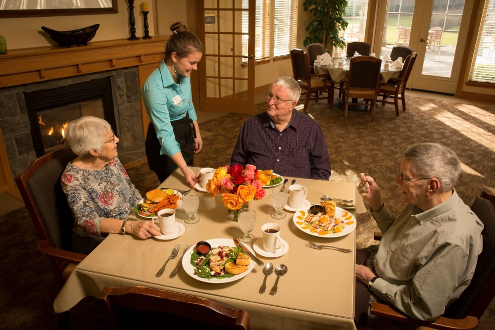 Residents being served in dining room at The Springs at Clackamas Woods in Milwaukie, Oregon.