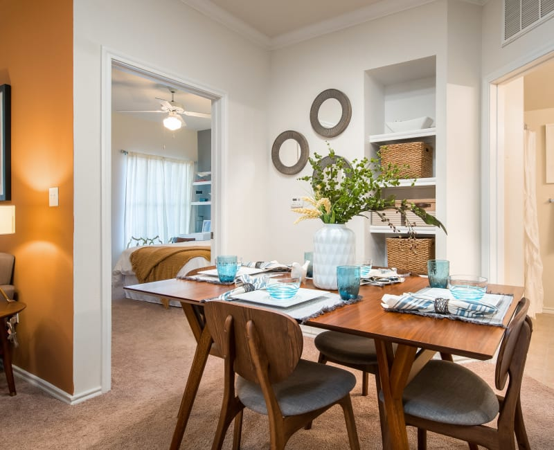 Well-furnished dining area in the open-concept floor plan of a model home at Rockbrook Creek in Lewisville, Texas
