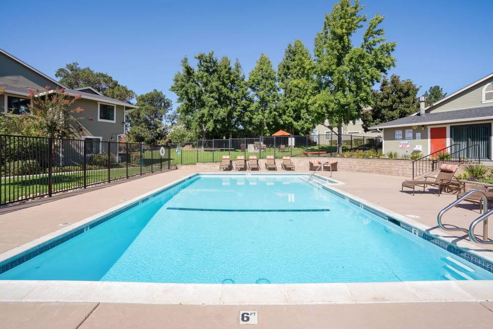 Spacious sundeck with table and chairs next to a swimming pool at Ridgecrest Apartment Homes in Martinez, California