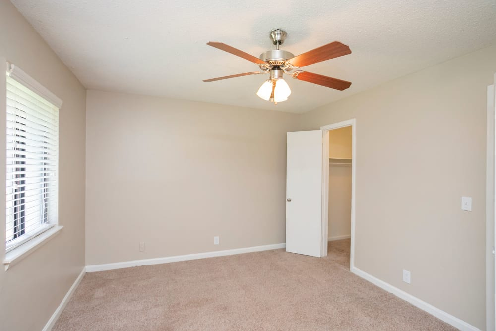 Carpeted bedroom with a ceiling fan at Magnolia Place Apartments in Franklin, Tennessee