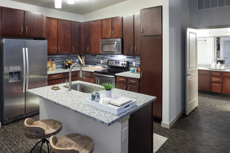 Gourmet kitchen with granite countertops and dark wood cabinetry in a model home at Regatta Sloan's Lake in Denver, Colorado