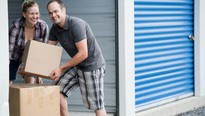 Man and woman move boxes into a self storage unit.