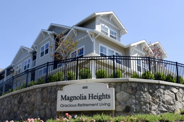 Building exterior and main sign at Magnolia Heights Gracious Retirement Living in Franklin, Massachusetts