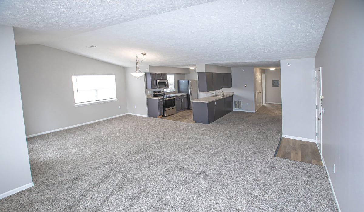 A large living with plush carpeting at Silver Lake Hills in Fenton, Michigan