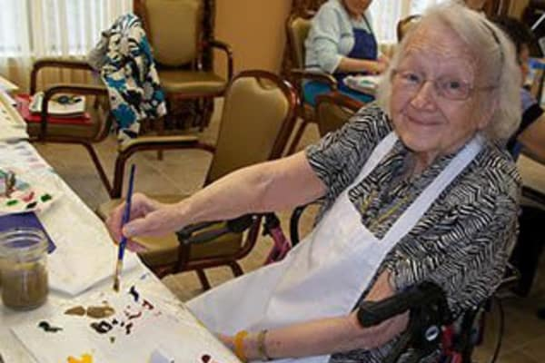 Woman paints at memory care at Discovery Commons At Spring Creek in Garland, Texas