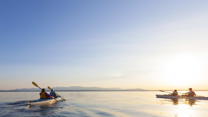 Two kayaks with two people in each paddling on a flat ocean surface with the sun shining and mountains in the distance