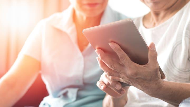 Two seniors looking at iPad