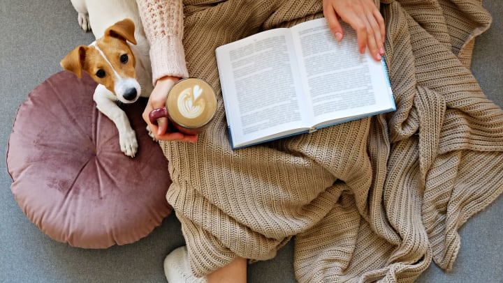 Woman with a blanket on her lap holding an open book and a latte and a dog sitting next to her on a cushion.