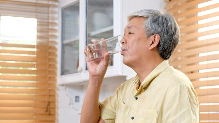 Senior man drinking a glass of water in a kitchen.
