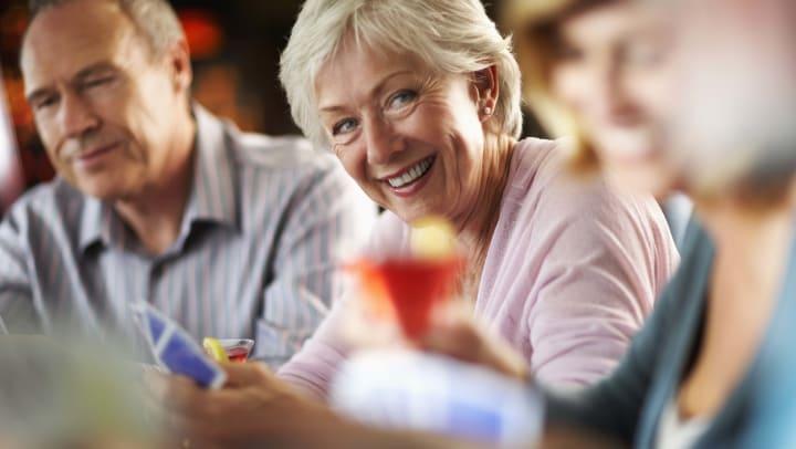 Senior woman having fun playing cards