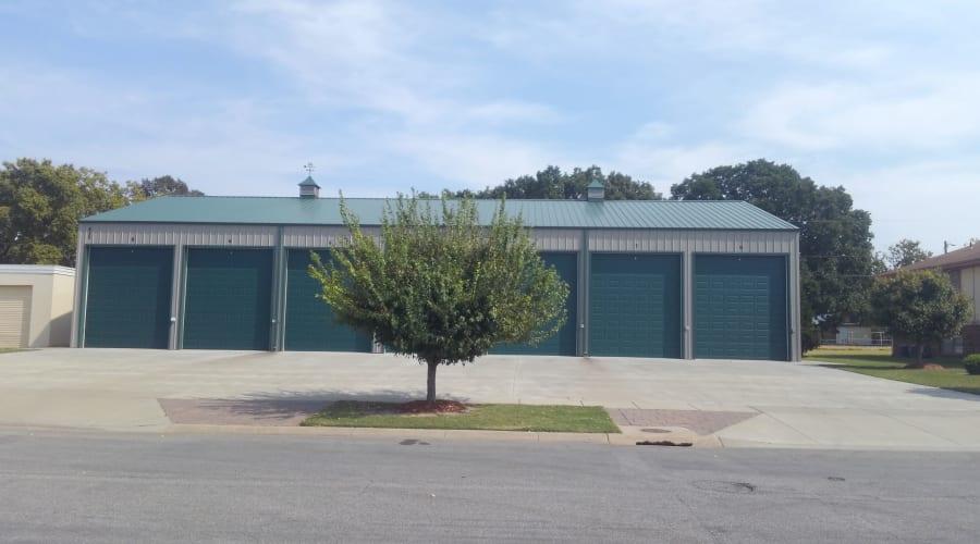 A tree in front of green storage units at KO Storage of Salina - Clark in Salina, Kansas