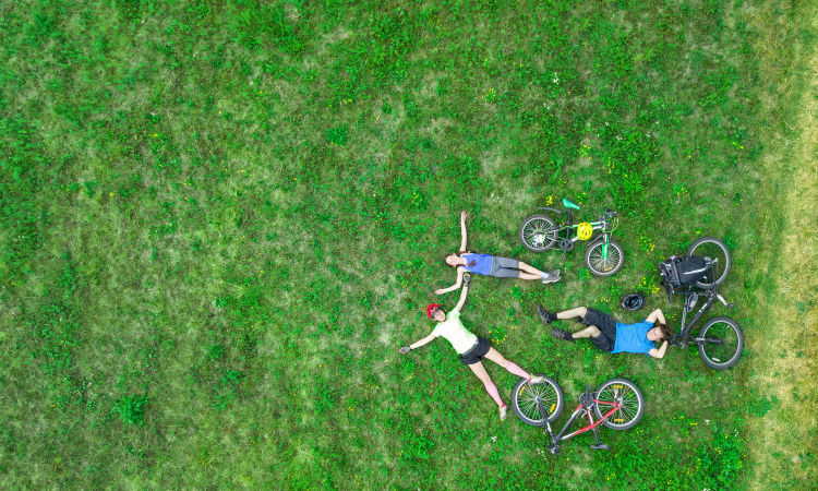 Residents relaxing on the grass during a bike ride near Evolv in Mansfield, Texas