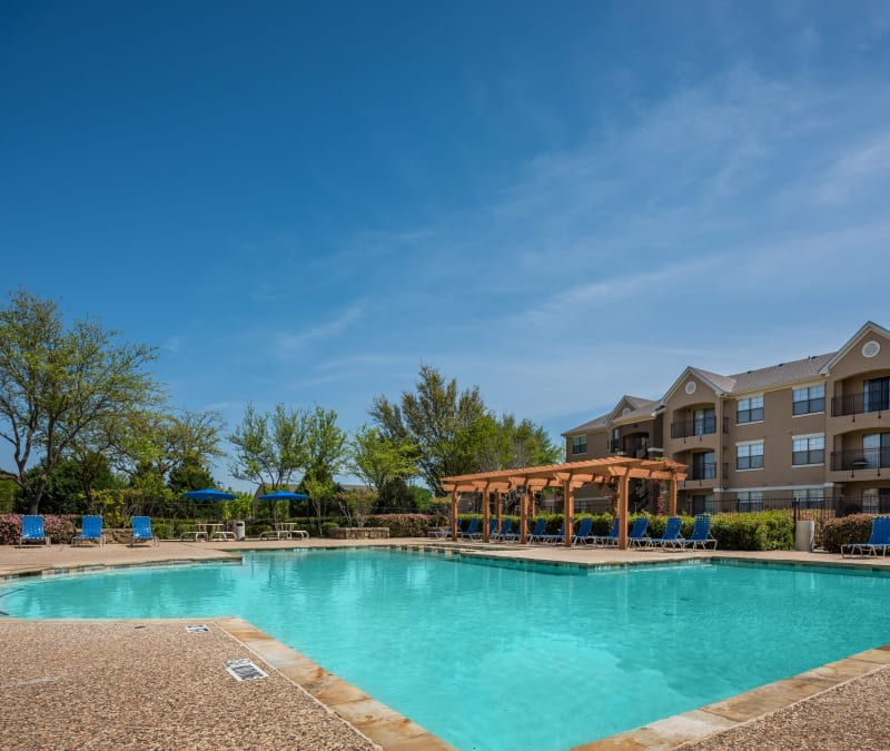 Beautiful swimming pool with plenty of lounge seating nearby at Arbrook Park Apartment Homes in Arlington, Texas