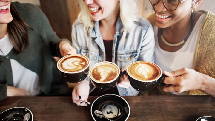 Three women smiling and holding up their coffee cups with foam art.