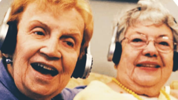 Two residents wearing headphones at  Quail Park Memory Care Residences of West Seattle