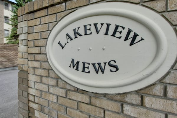 Close-up of a brick wall with a Lakeview Mews sign in Calgary, AB