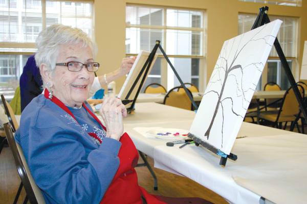 Resident painting a tree in an art class at Ashton Gardens Gracious Retirement Living in Portland, Maine