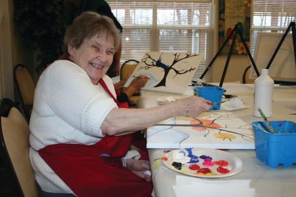 A happy resident painting at Guelph Lake Commons in Guelph, Ontario