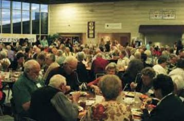 Overcrowded tables of seniors eating dinner
