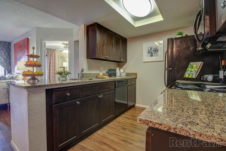 Kitchen with granite counter tops and hardwood floors at Casa Santa Fe Apartments in Scottsdale, Arizona