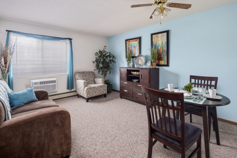 A spacious living room and personal dining area at Parkside of Livonia in Livonia, Michigan